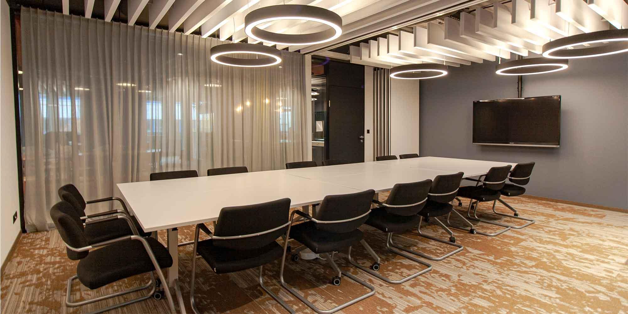 Dieses Sitzungszimmer ist mit mehreren Ringostar Pendeleluchten von lightnet ausgestattet. Diese geben eine optimale Grundbeleuchtung und die Leuchte wirkt als element der Raumgestaltung