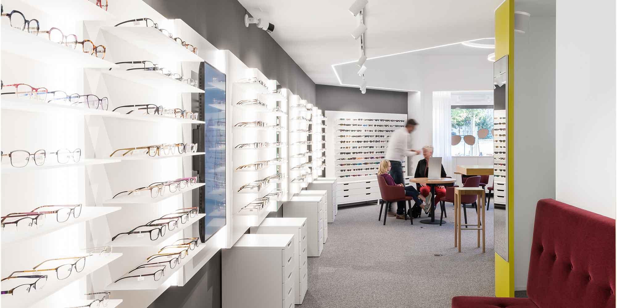 Nahaufname der Ladengestelle mit den Brillen eines Optikergeschäftes. die Stromschienenstrahler leuchten die Gestelle optimal aus.