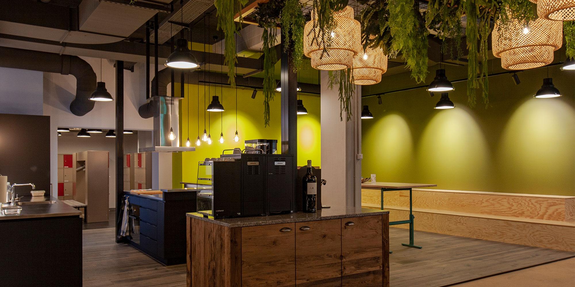 Die Küche und den Aufenthaltsraum wurden mit dekorativen Pendelleuchten aus Bambus passend zum Junglelook Ausserdem trendige Industrie Pendelleuchten wurden als Kontrast eingesetzt. Stromschienenstrahler beleuchtet die olivgrünen Wände.