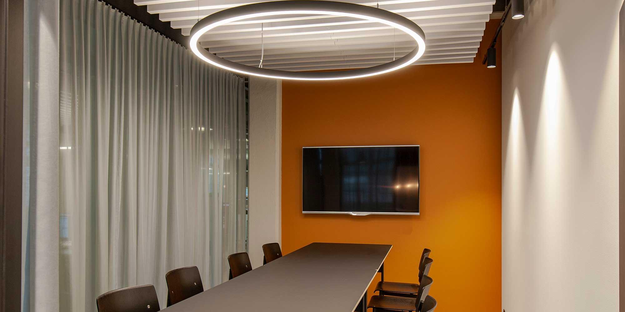 Die architektonische Leuchte von Lightnet, Ringo Star, wurde als Grundbeleuchtung gewählt. Die Wände werden mit Stromschienenstrahler ausgeleuchtet. Der lange Sitzungstisch wurde mit einen grossen Screen ergänzt, damit der kreativen Brainstormings nichts mehr im Wege steht. Der graue Vorhang dient der Diskretion.