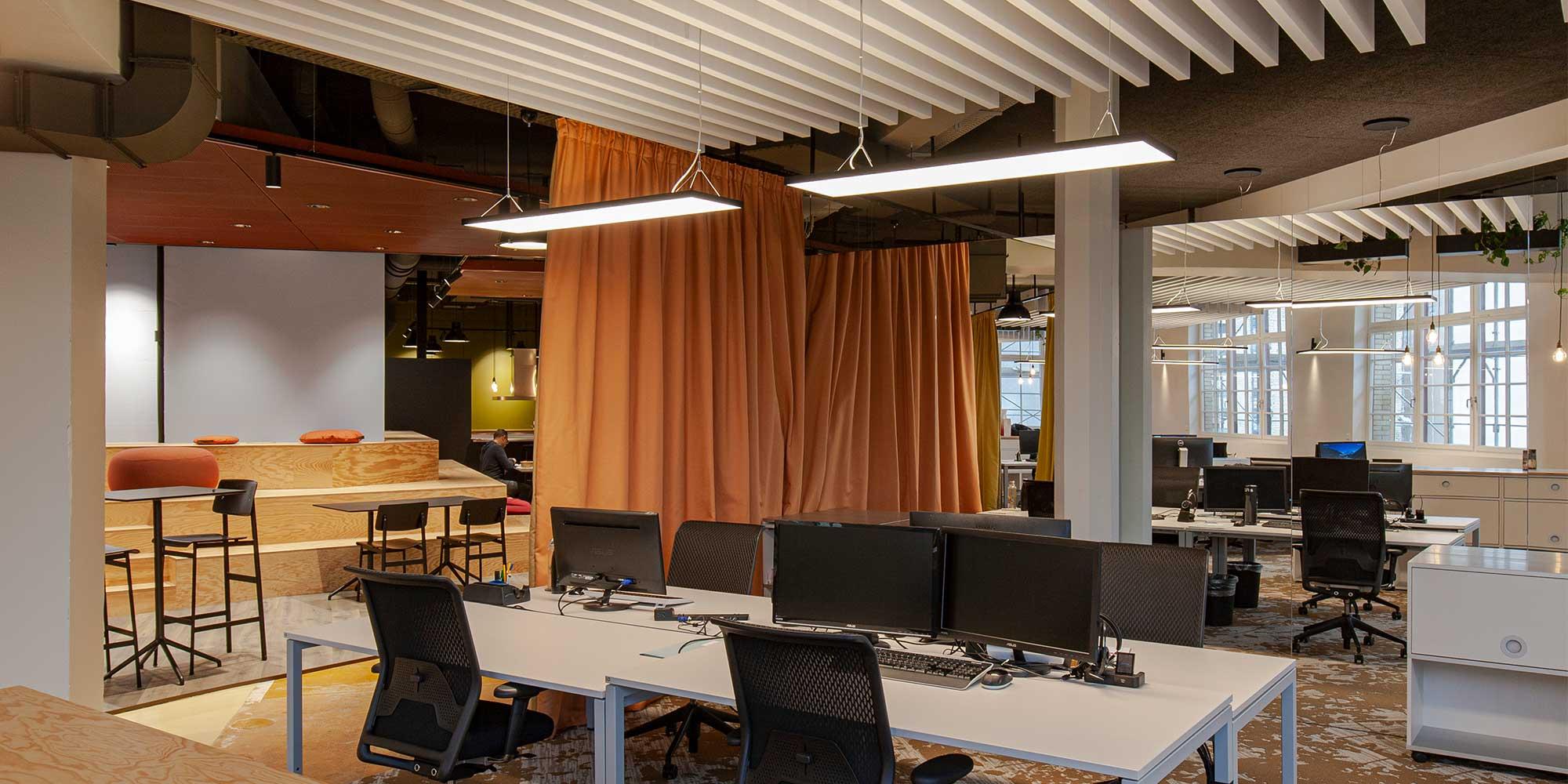 Über den Arbeitsplätzen im Grossraumbüro hängen rechteckige architektonische Leuchten von Lightnet. Cubic Pendelleuchten passen ideal zu den eckigen Schreibtischen. Zwischendurch werden Industrie Pendelleuchten oder Filament Leuchten eingesetzt.