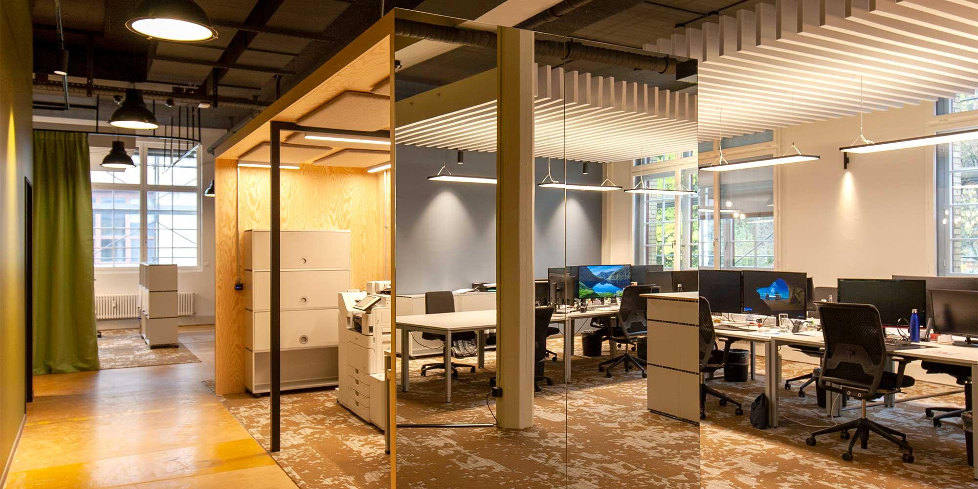 Das Grossraumbüro wird durch Spiegelglaswände abgetrennt. Arbeitsplätze werden perfekt mit den Cubic Langfeldleuchten ausgeleuchtet, Der Druckerraum ist mit Akkustikplatten an der Decke ausgestattet und passend dazu die Matric A1 Anbauleuchte. Der Gang mit Industrieleuchten ausgestattet.