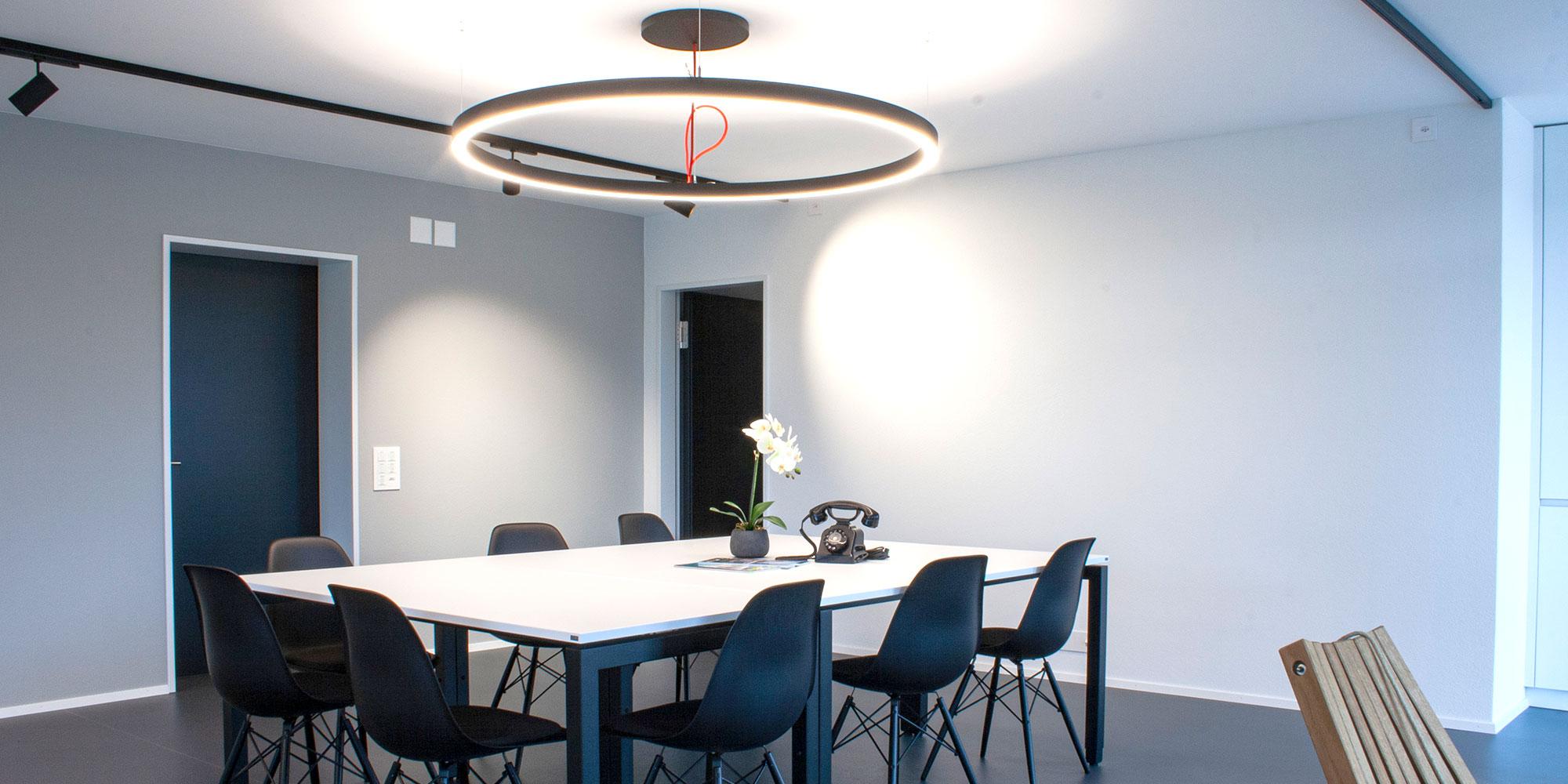 Sitzungszimmer der wiederkehr elektro ag mit der ringo star Pendelleuchte als Blickfang in den Corpporate Identity Farben. Die Stromschienenstraher leuchten die Wände perfekt aus.
