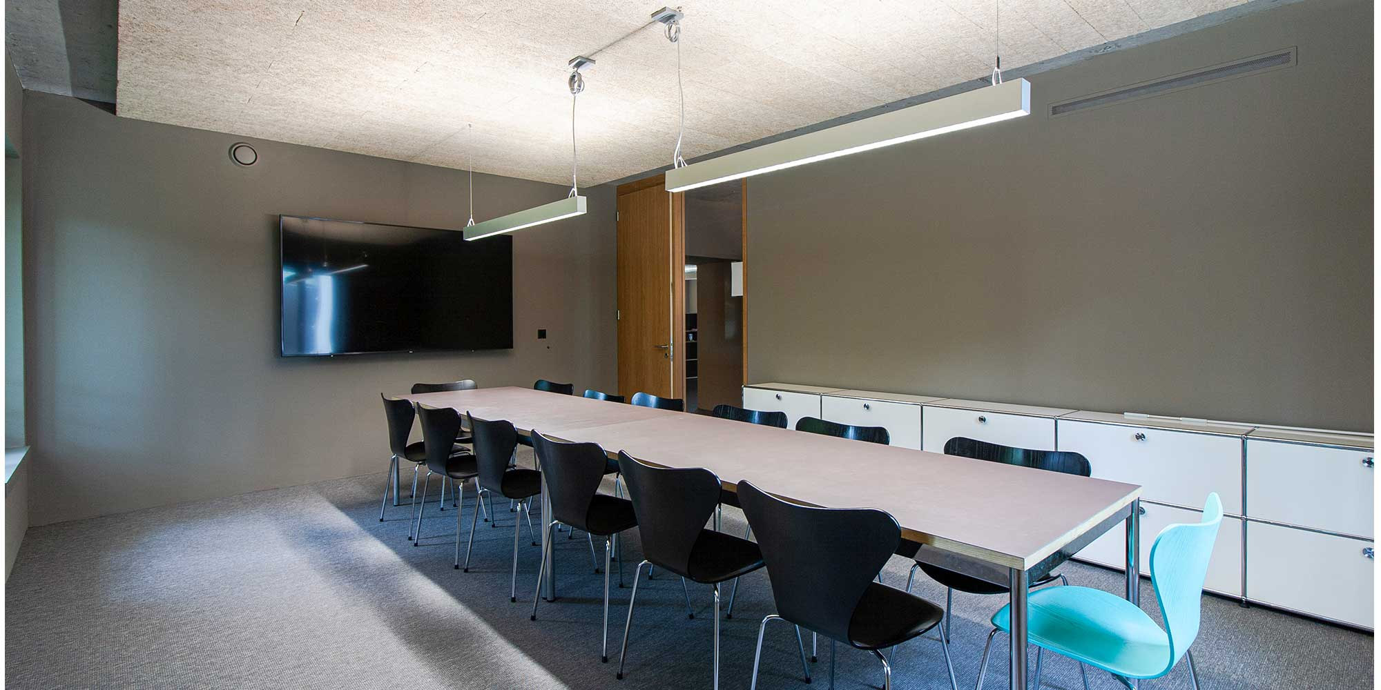 Seitliche Ansicht des Sitzungsraumes. Der Tisch wird mit der Matric Pendelleuchte von Lightnet optimal ausgeleuchtet